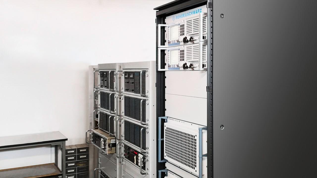 Confronto tra nuovo e vecchio: la potenza di trasmissione di 1 kW richiede una certa quantità di spazio anche con la tecnologia moderna (davanti), soprattutto se i componenti sono ridondanti per motivi di sicurezza. Il vecchio sistema (dietro) occupava fino a due rack.